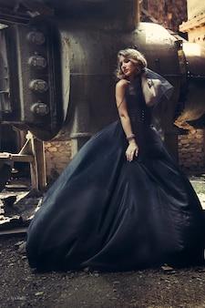 Blondes mädchen in der schwarzen kleideralten verlassenen fabrik