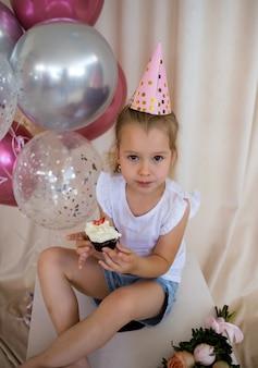 Blondes mädchen in einem festlichen hut sitzt mit einem cupcake mit einer kerze auf einem festlichen hintergrund mit einem platz für text
