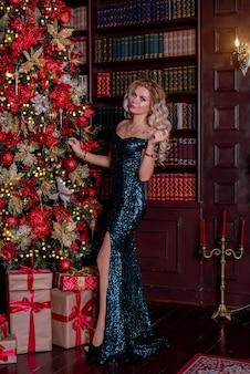 Blondes mädchen in einem kleid, das nahe einem weihnachtsbaum in einem vintagen interieur aufwirft, das für das neue jahr verziert wird