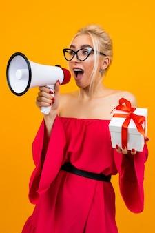 Blondes mädchen in einem roten kleid spricht über eine auslosung mit einem megaphon und einer geschenkbox in händen auf einer gelben oberfläche