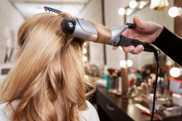 Blondes mädchen in einem schönheitssalon, der eine frisur tut. verdrehen von haarsträhnen auf einem styler. nahansicht.