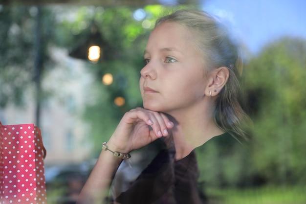 Blondes mädchen in einem schwarzen kleid sitzt in der straßenbahn