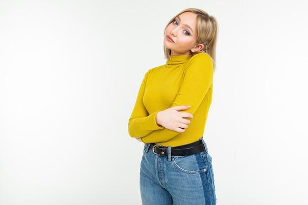 Blondes mädchen in einer eng anliegenden gelben jacke und in jeans, die seitlich auf einem weißen hintergrund aufwerfen