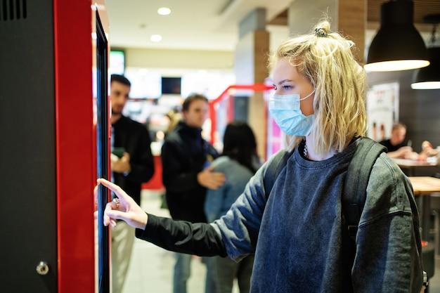 Blondes mädchen in einer medizinischen maske wählt essen auf dem bildschirm in einem restaurant aus