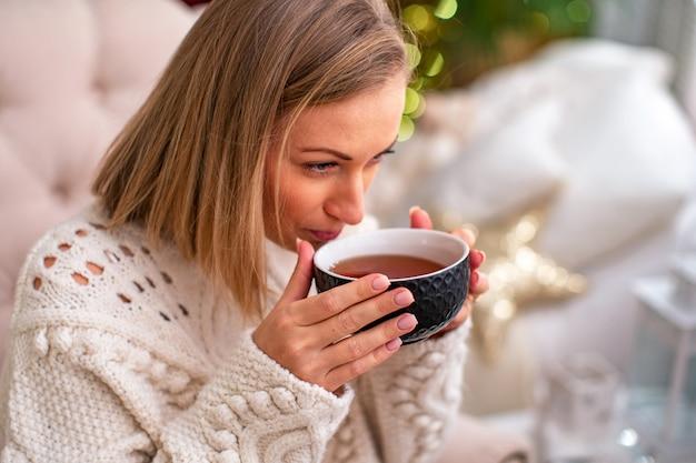 Blondes mädchen in einer strickjacke mit einer tasse tee sitzend auf dem bett