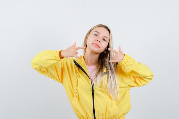 Blondes mädchen in gelber jacke, das rocksymbol tut und elegant aussieht