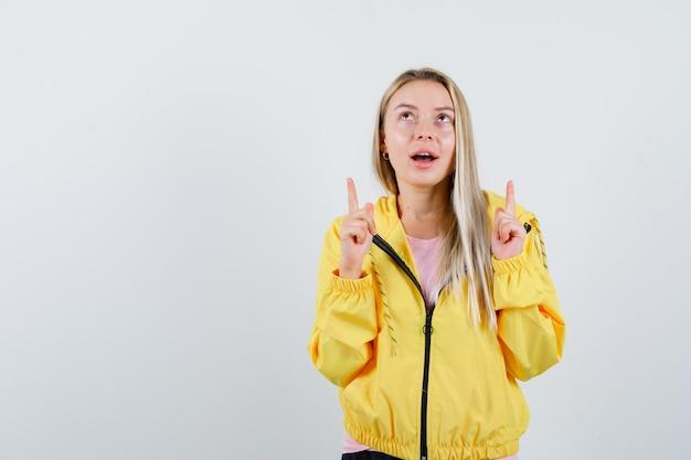 Blondes mädchen in gelber jacke zeigt nach oben und sieht hoffnungsvoll aus