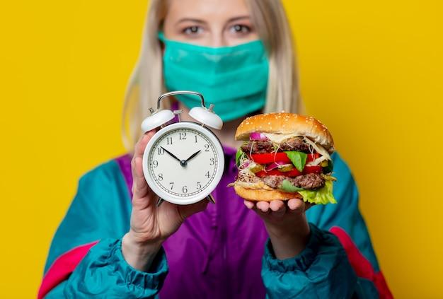 Blondes mädchen in gesichtsmaske mit burger und wecker