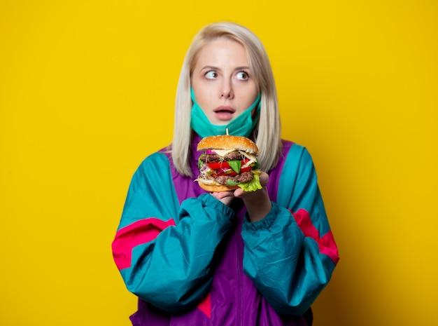 Blondes mädchen in gesichtsmaske mit burger