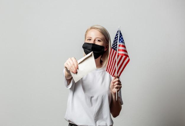 Blondes mädchen in gesichtsmaske mit usa-flagge und geld