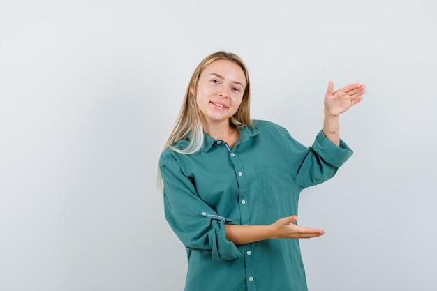 Blondes mädchen in grüner bluse mit schuppengeste und glücklichem blick