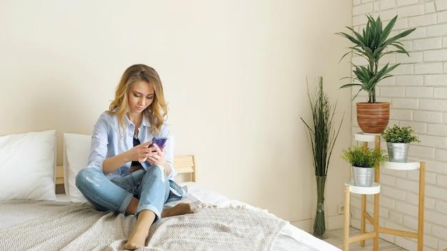 Blondes mädchen in jeans sitzt auf dem bett und arbeitet am smartphone