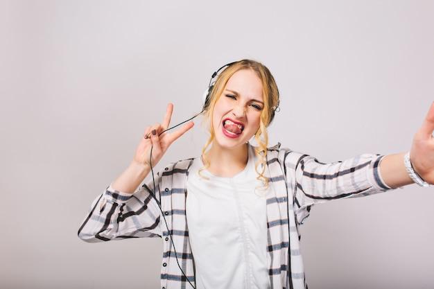Blondes mädchen in kopfhörern mit herausstehender zunge genießt musik und narren herum, die isoliert tanzen. attraktive junge frau mit lockigem haar, die lieblingslied hört und spaß hat