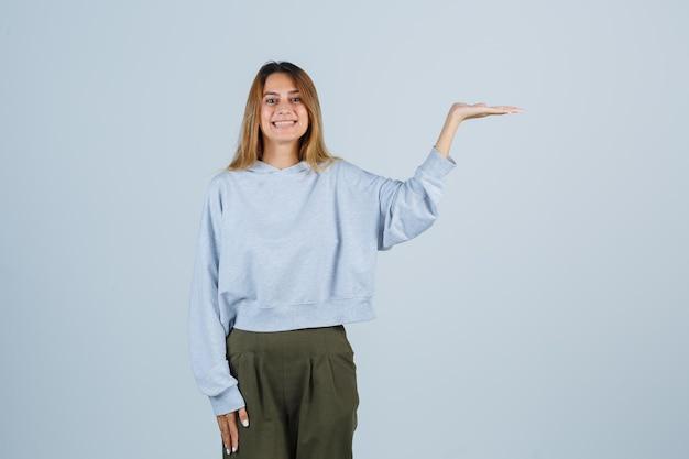 Blondes mädchen in olivgrünem blauem sweatshirt und hosen, die hände ausstrecken, als etwas halten und strahlend aussehen, vorderansicht.