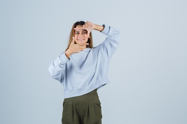 Blondes mädchen in olivgrünem blauem sweatshirt und hosen, die kamerageste zeigen und strahlend aussehen, vorderansicht.