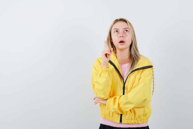 Blondes mädchen in rosa t-shirt und gelber jacke, das den zeigefinger in der heureka-geste hebt, während sie die hand am ellbogen hält und nachdenklich aussieht