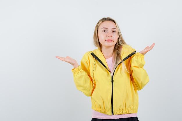 Blondes mädchen in rosa t-shirt und gelber jacke, das sich fragend die hände ausstreckt und verwirrt aussieht