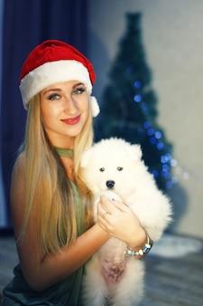Blondes mädchen in roter weihnachtsmütze mit samojede-husky-hund in weihnachtsdekorationen