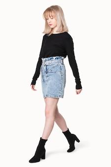 Blondes mädchen in schwarzem pullover und jeansrock für winterbekleidungsshooting