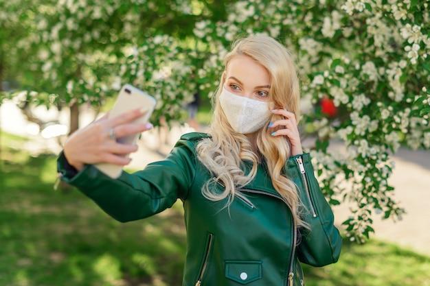 Blondes mädchen in weißer medizinischer maske und grüner jacke hält weißes smartphone in ihren händen und nimmt selfie,