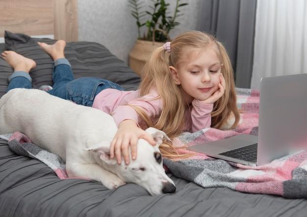 Blondes mädchen lernt zu hause online mit einem laptop. kinder und ein hund auf dem bett.