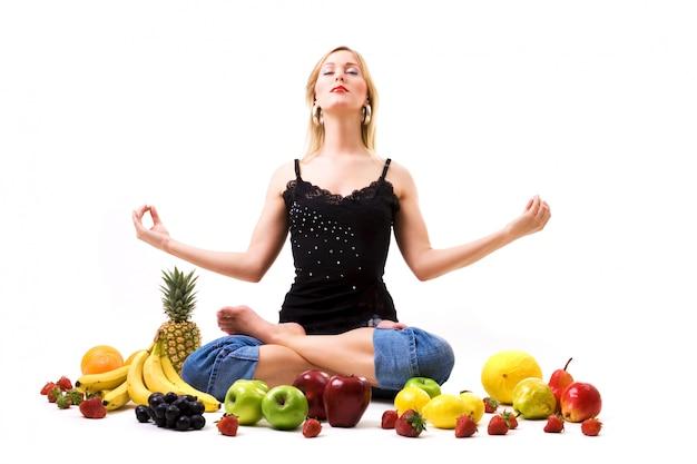 Blondes mädchen meditiert umgeben von früchten