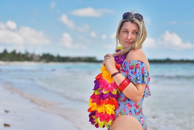 Blondes mädchen mit blumenhalskette posiert am meer in mexiko