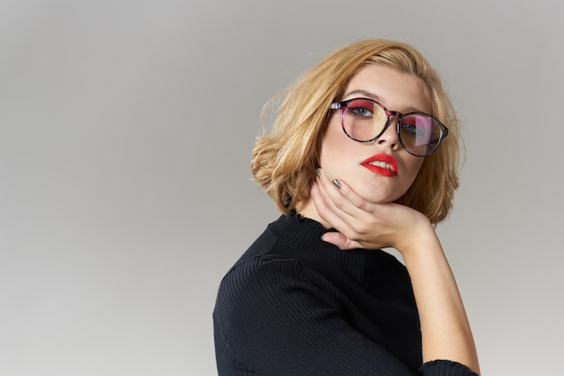 Blondes mädchen mit brille rote lippen schwarze bluse beschnitten ansicht glamour licht hintergrund studio.