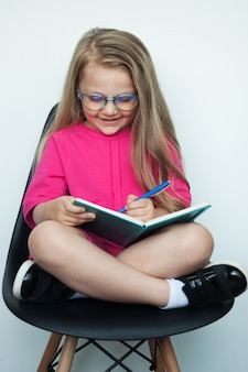 Blondes mädchen mit brille schreibt etwas in ein buch, während in einem sessel auf einer weißen wand posiert