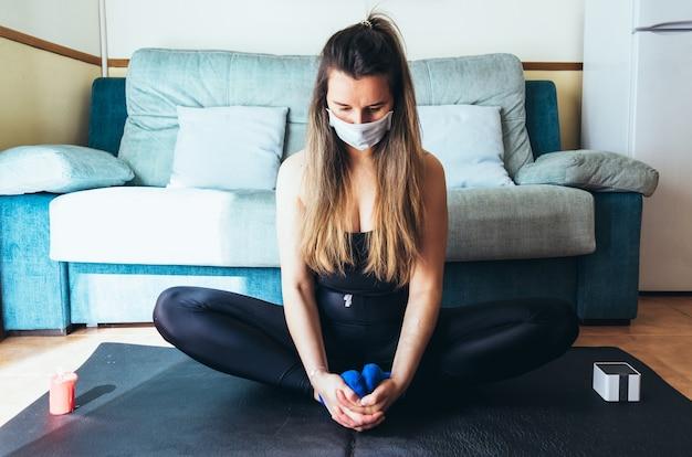 Blondes mädchen mit der chirurgischen maske, die yoga und meditation zu hause tut.