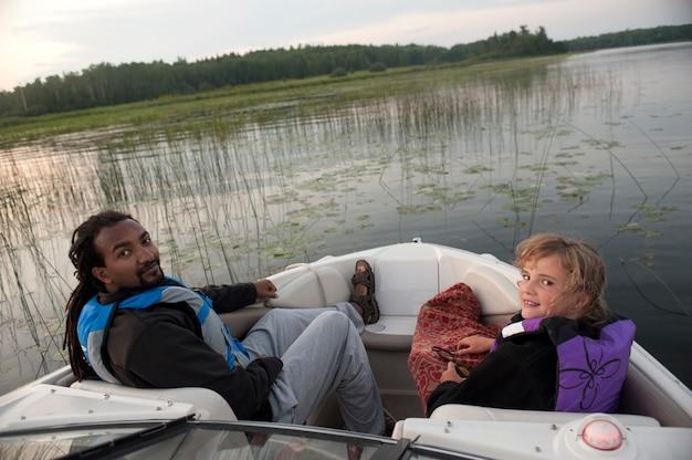 Blondes mädchen mit einem amerikanischen africianmann am bogen eines bewegungsbootes im see des holzes, ontario
