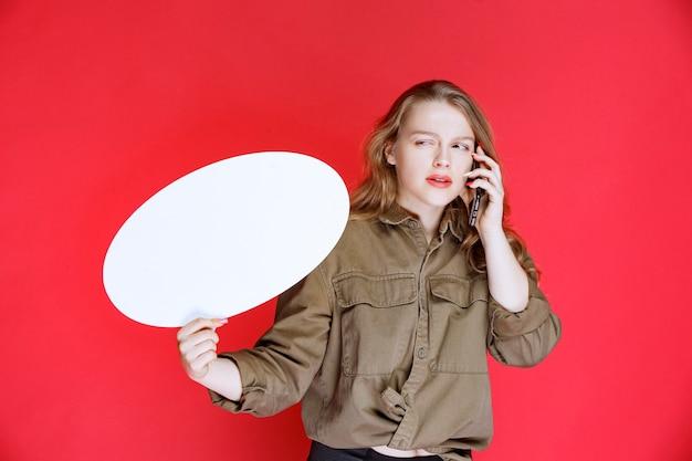 Blondes mädchen mit einem ovalen thinkboard im gespräch mit dem telefon.