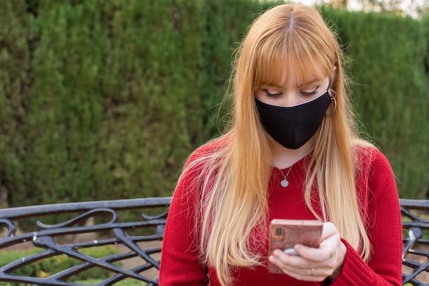 Blondes mädchen mit gesichtsmaske und rotem pullover, der auf einer parkbank sitzt. mit dem telefon surfen