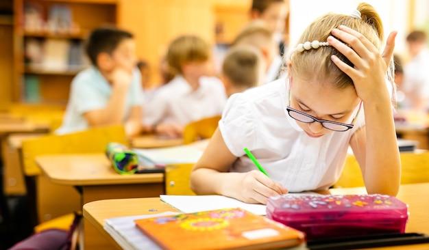 Blondes mädchen mit großen gläsern, die im klassenzimmer sitzen, studieren, lächeln. grundschulbildung, erster schultag.