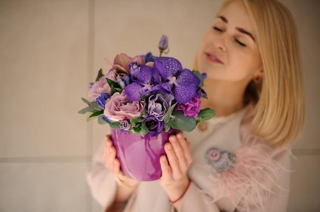 Blondes mädchen mit iris im blumentopf