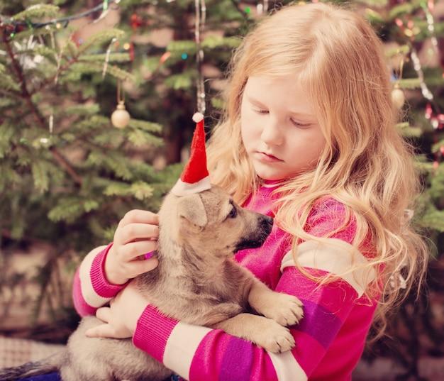 Blondes mädchen mit kleinem hund im roten weihnachtshut