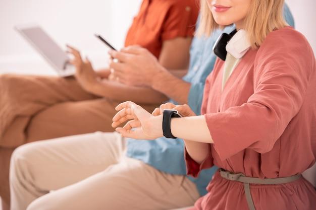 Blondes mädchen mit kopfhörern, die smartwatch auf ihrem linken handgelenk betrachten, während sie unter ihren erholsamen freunden sitzen, die mobile geräte verwenden