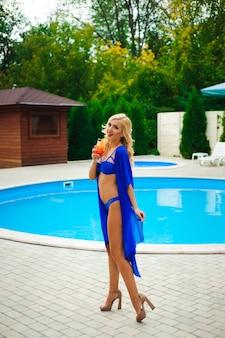 Blondes mädchen mit langem haar, das cocktail hält und nahe pool auf der sonne aufwirft