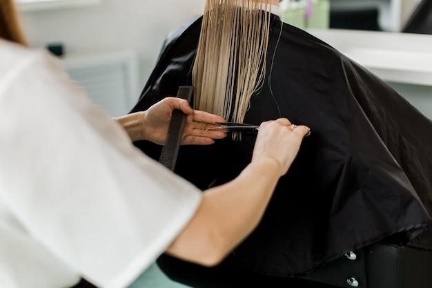 Blondes mädchen mit langen glatten haaren sitzt auf einem stuhl in einem schönheitssalon. schwarzes gewand. blick von hinten.