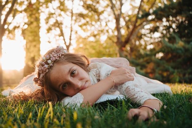 Blondes mädchen mit lockigem haar, gekleidet im kommunionkleid, das für fotos auf dem gras liegt