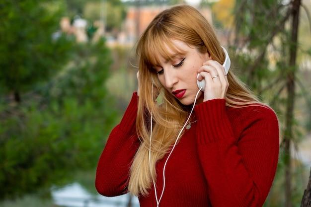 Blondes mädchen mit rotem lippenstift und rotem pullover, der musik mit kopfhörern im park hört.