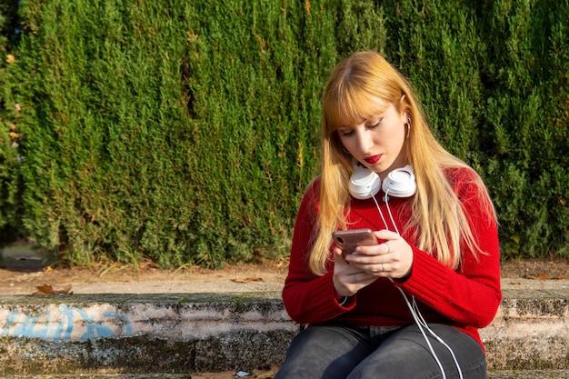 Blondes mädchen mit rotem lippenstift und rotem pullover, der musik mit telefon und kopfhörern im park hört.