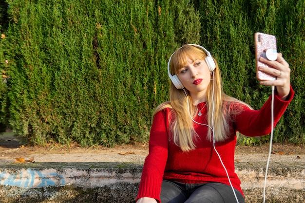 Blondes mädchen mit rotem lippenstift und rotem pullover macht sich ein foto mit kopfhörern im park.