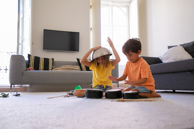 Blondes mädchen mit schüssel auf kopf spielt mit freund. fröhlicher kleiner junge klopft an pfannen. zwei glückliche kinder sitzen auf dem boden und haben spaß zusammen im wohnzimmer. kindheits-, ferien- und wohnkonzept