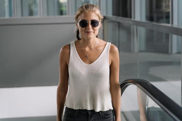 Blondes mädchen mit sonnenbrille, die eine rolltreppe klettert