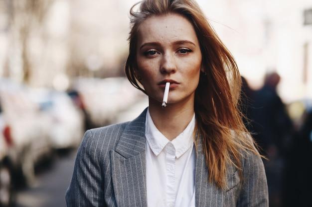 Blondes mädchen mit zigarre steht auf der straße