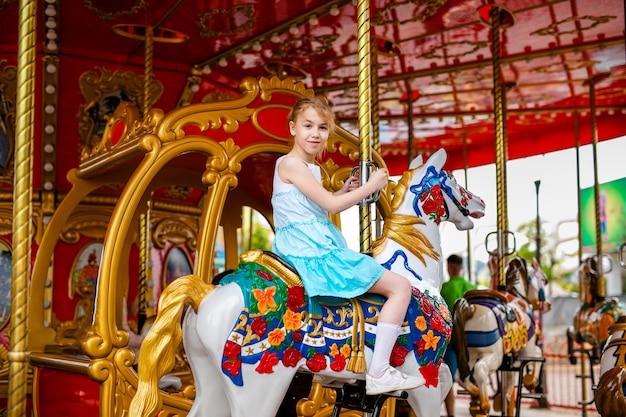 Blondes mädchen mit zwei borten im weißen und blauen kleid, das buntes pferd im karussell reitet.