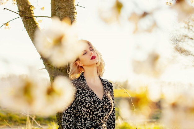 Blondes mädchen nahe blühendem baum an der landschaft im sonnenuntergang
