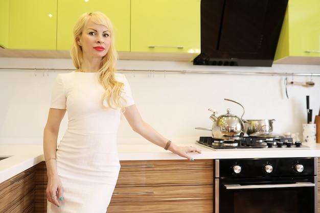 Blondes mädchen posiert vor der kamera in der küche neben schränken