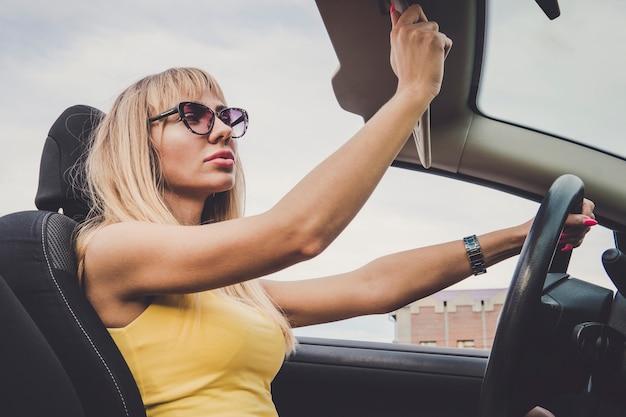 Blondes mädchen schaut in den spiegel und putzt sich. junge fröhliche frau, die auto fährt. eine frau bewundert ihre schönheit im spiegelbild. frau senkt die sonnenblende und hält das lenkrad